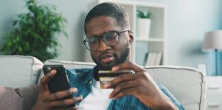 homem com cartao e celular na mao