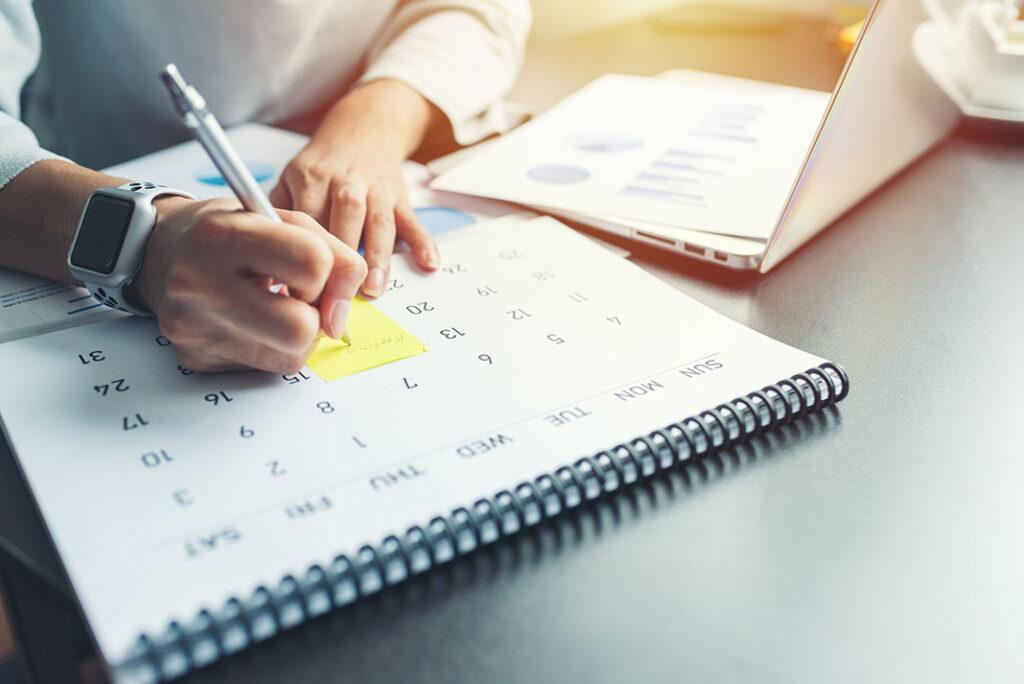 Pessoa escrevendo em um calendário
