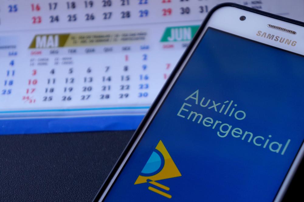 tela de celular com app do auxilio emergencial e calendário ao fundo
